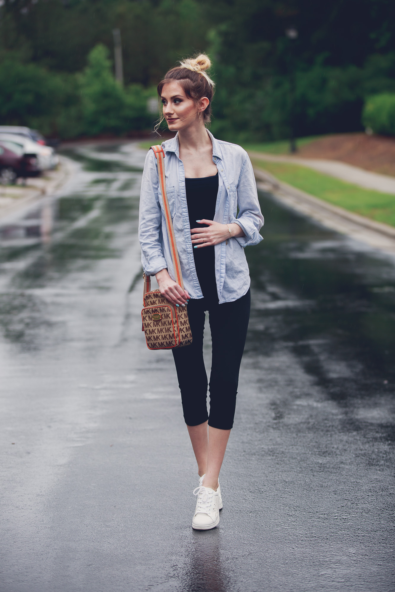 Fashion and lifestyle blogger Jessica Linn from Linn Style wearing a casual outfit: Target maternity leggings, an aeropostale tank top, and chambray button up, Target tennis shoes, Charming Charlie's earrings, and a Michael Kors purse in Cary North Carolina