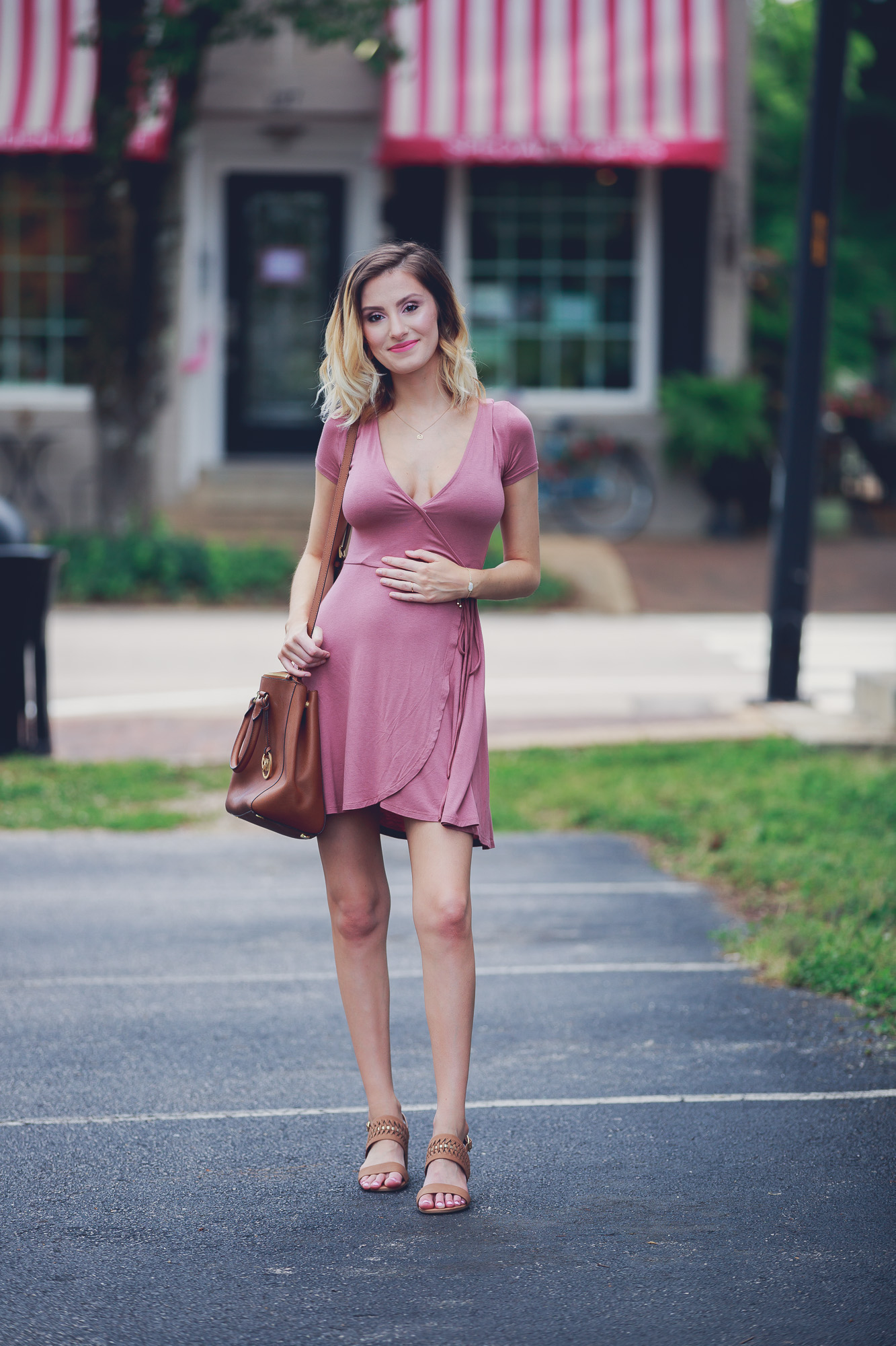 Lifestyle and Fashion blog Linn Style bye Jessica Linn Outfit of the Day post and summer outfit inspiration wearing a mauve Forever21 wrap dress (great for pregnancy) a Dogearred jewelry lotus necklace, a Kendra Scott bracelet, World Market earrings, brown low sandal heels from Ross, and carrying a Michael Kors tan purse while walking in Historic Downtown Cary North Carolina.