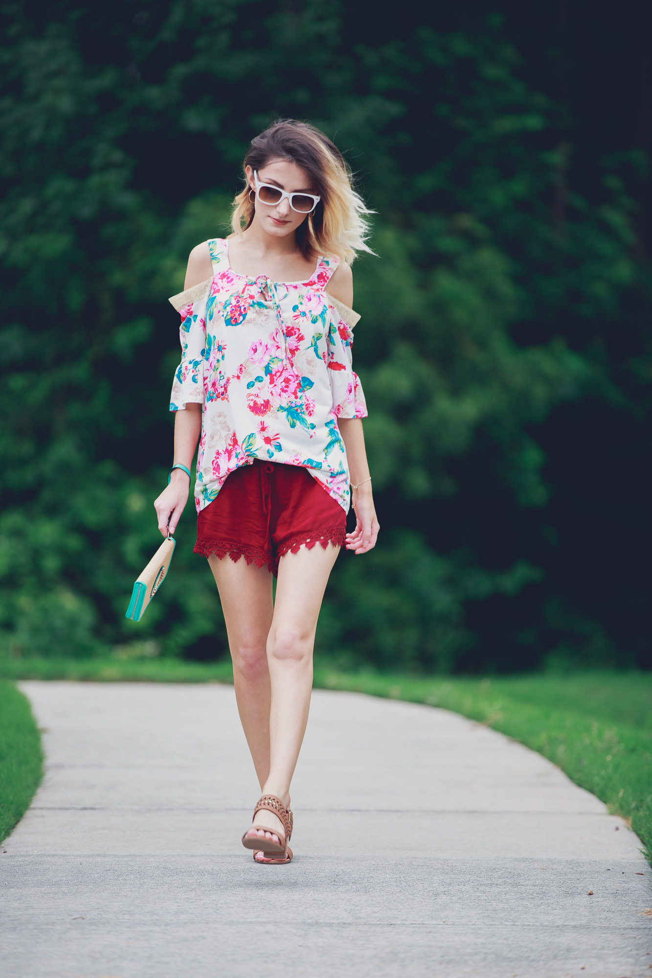 Lifestyle and fashion blogger Jessica Linn from Linn Style wearing a cold shoulder floral blouse, lace hemmed maroon shorts, low brown heels, and a teal and gold pineapple wristlet from Ross. Sunglasses from and earrings from Charming Charlie's