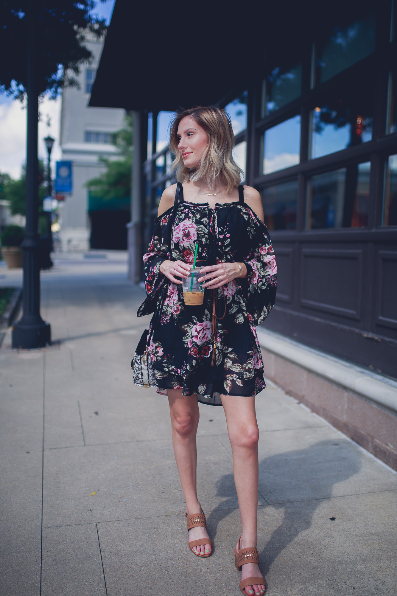 Fashion, lifestyle, and beauty blogger / vlogger Jessica Linn from Linn Style wearing an off the shoulder black floral mid thigh dress with Matisse footwear heels, a coach purse, and a Mamma Bear necklace from CY Design Studio