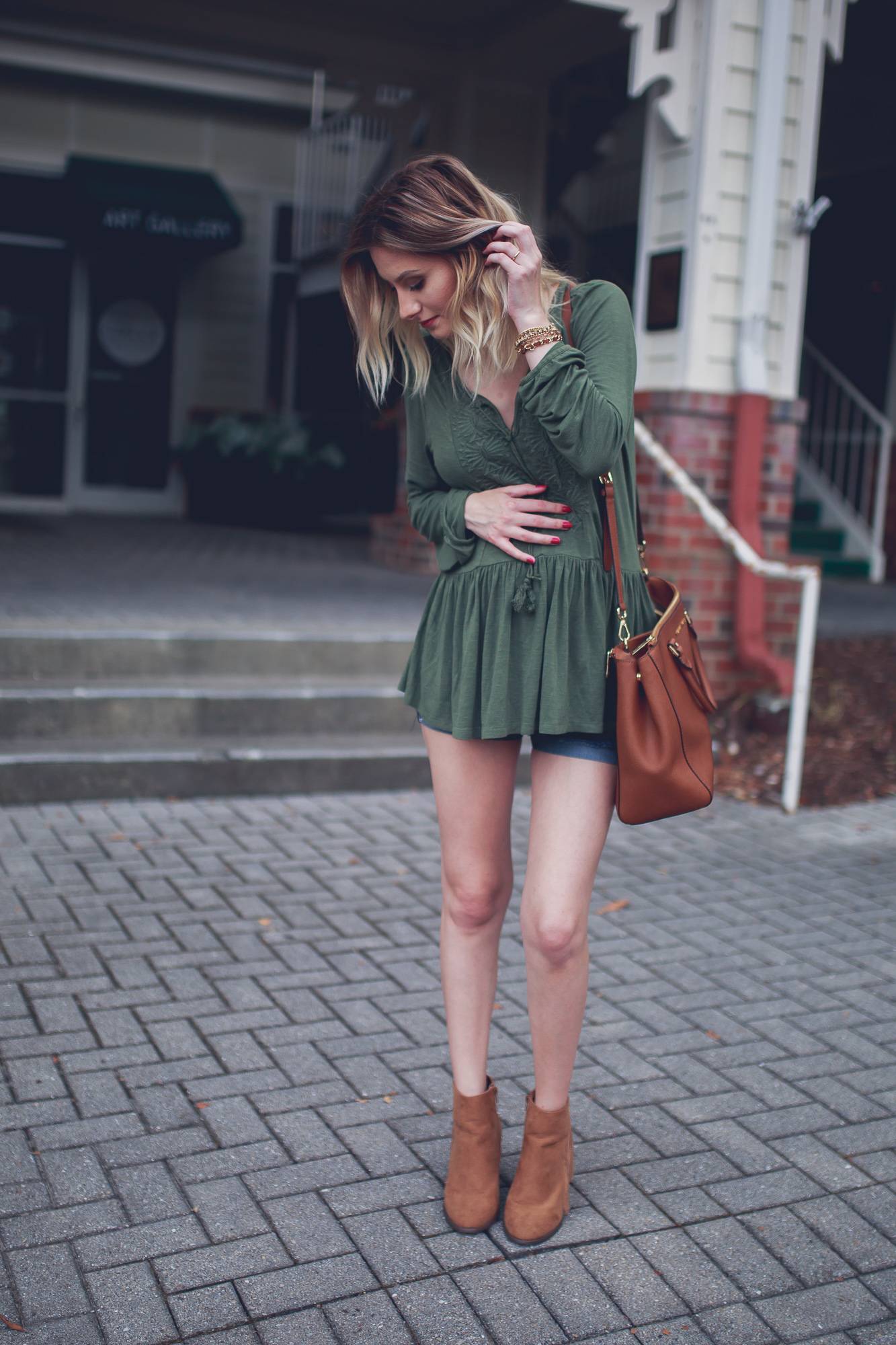 Lifestyle and fashion blogger Jessica Linn from Linn Style wearing a flow green peasant blouse from Express, maternity shorts, forever21 faux suede fringed booties, a brown Micheal kore purse and a necklace from CY Design Studio in Downtown Cary North Carolina