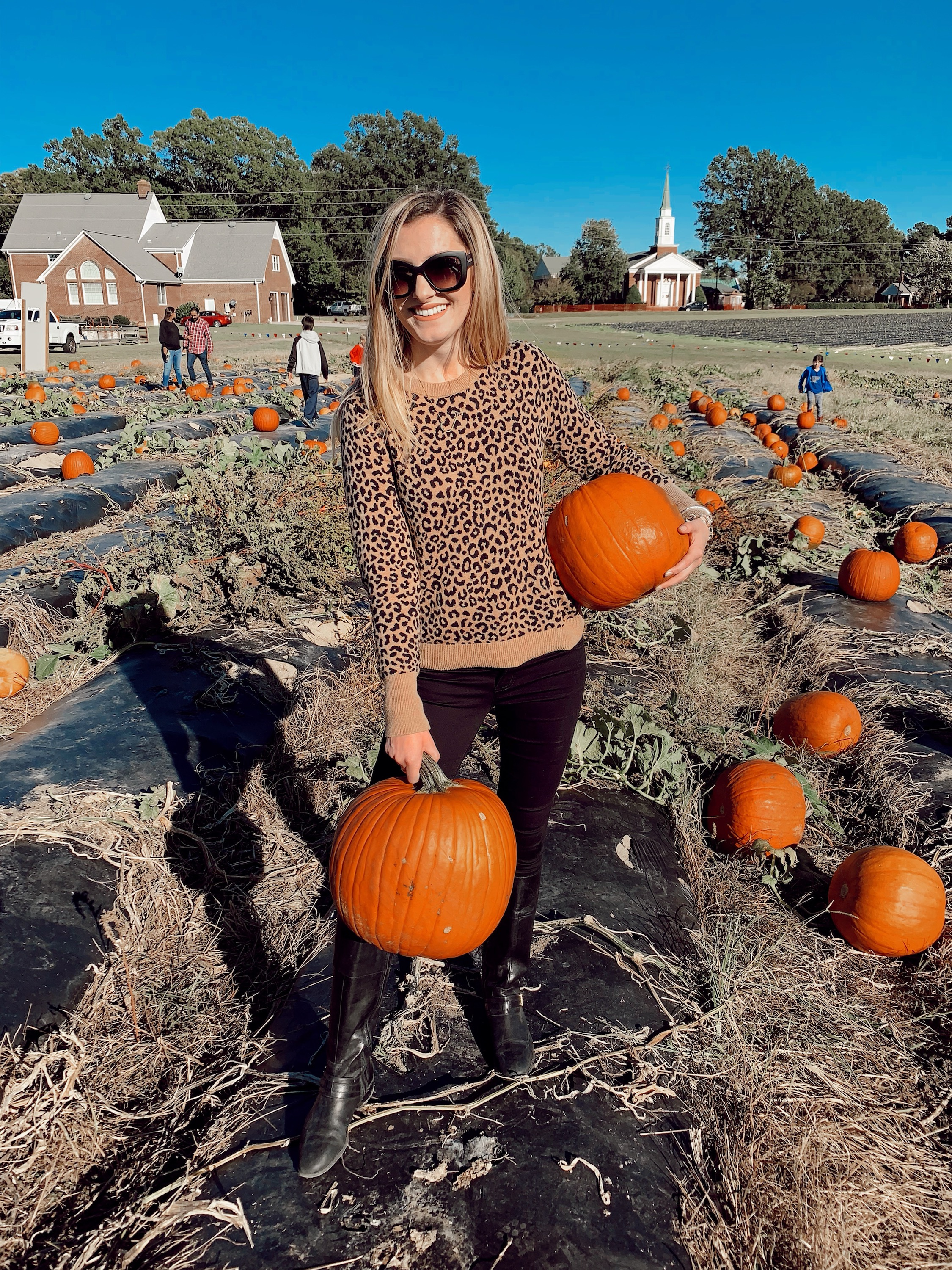 The $20 Target Pullover Sweater You'll Want In Every Print | North Carolina fashion and lifestyle blogger, Jessica Linn, wearing a leopard print pullover sweater from Target, black Charlotte Russe jeans, Ralph Lauren boots, and Eli Tahari sunglasses at Phillips Farm Cary NC.