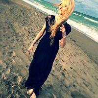 North Carolina fashion and lifestyle blogger Jessica Linn wearing a navy blue maxi dress, silver sandals, an da feather pendant necklace on a beach in Florida.