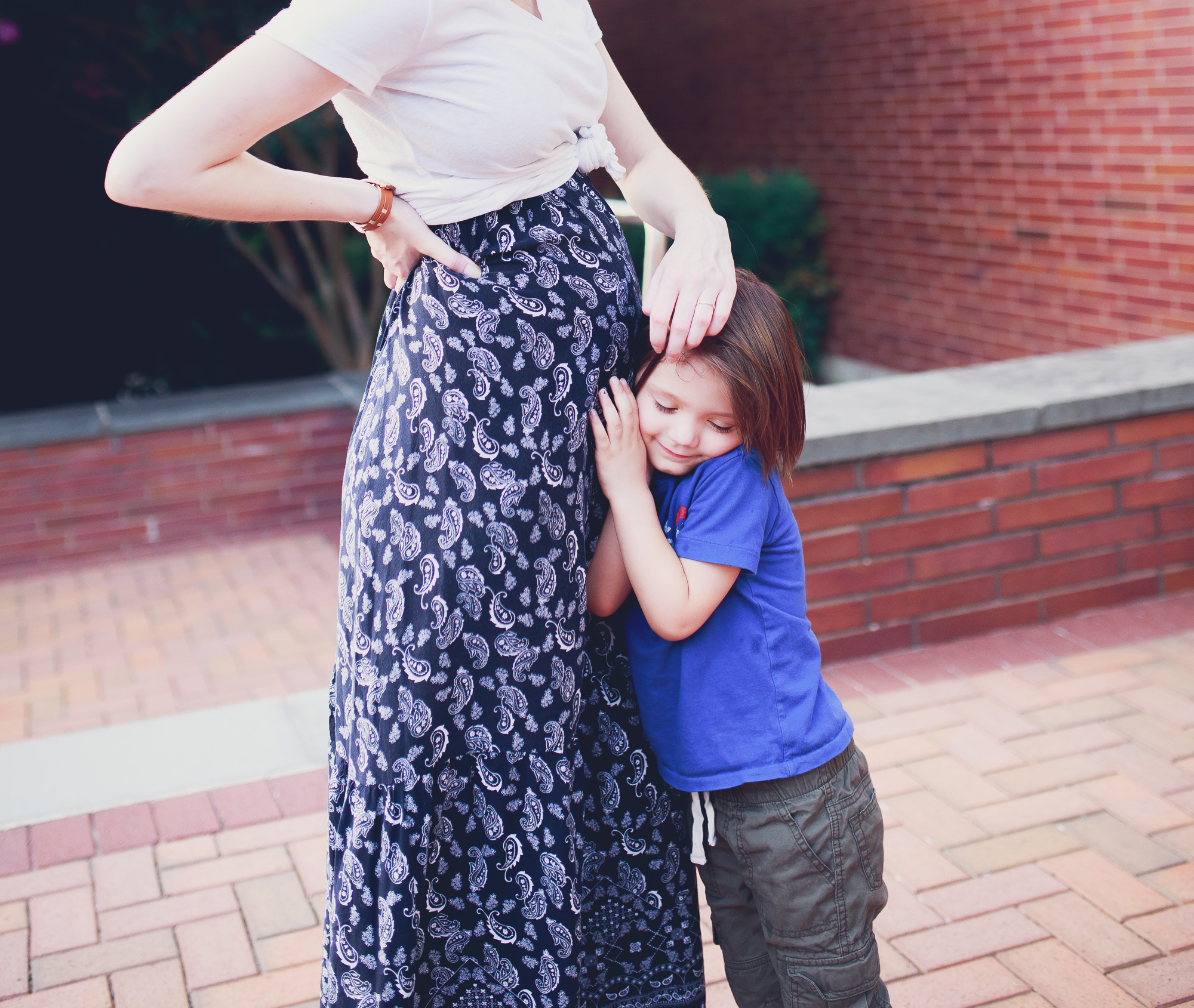 Fashion, lifestyle, and beauty blogger / blogger Jessica Linn from Linn Style wearing a Forever21 navy blue and white paisley sundress with a tied white t-shirt to show baby bump with Tory Burch sandals. Pregnancy Fashion Maternity