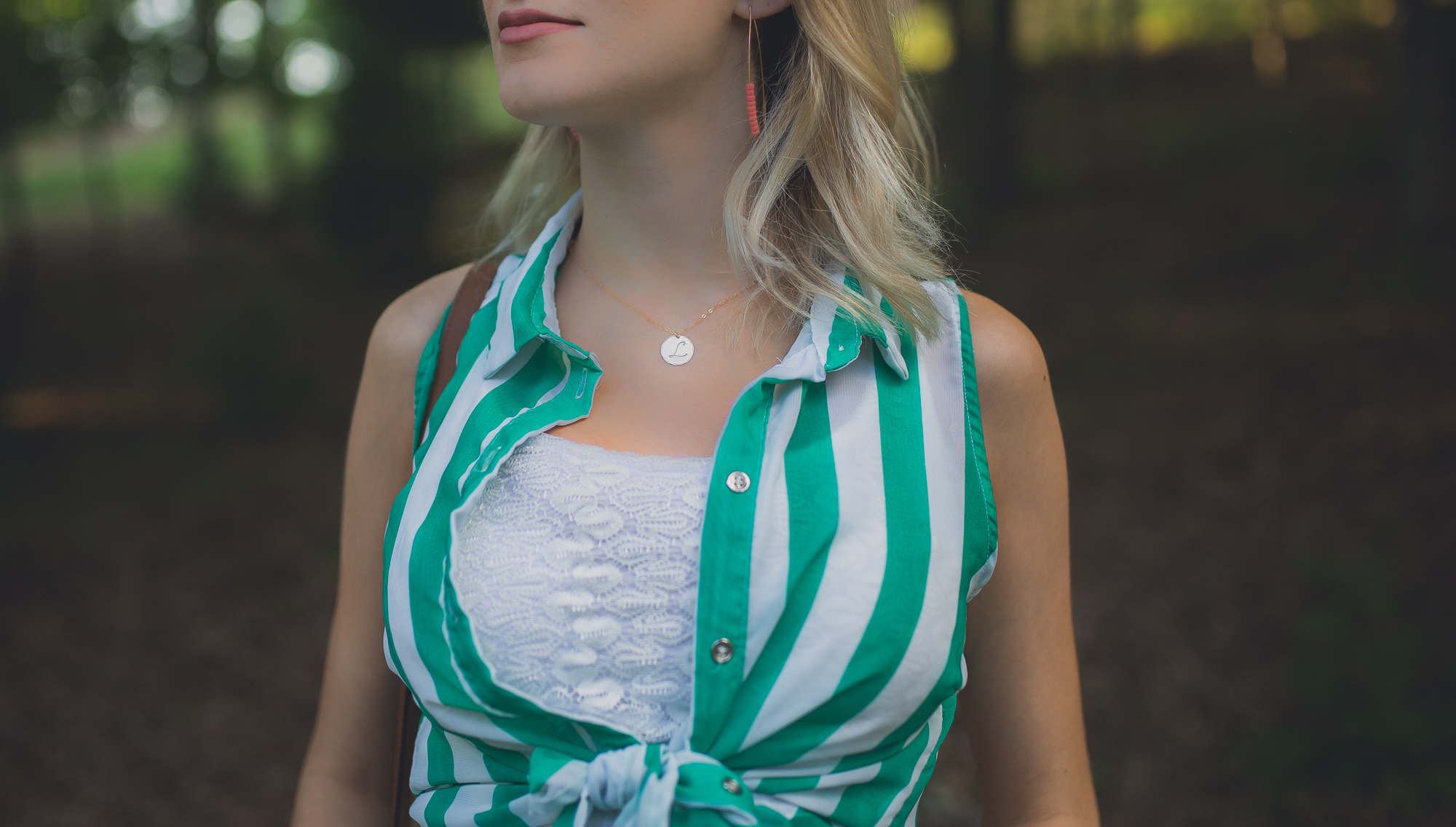 Fashion, lifestyle, and beauty blogger/ vlogger wearing maternity fashion a white sundress with green stripe accents and jewelry from CY Design Studio and Tory Burch Sandals.