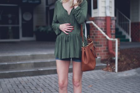 Lifestyle and fashion blogger Jessica Linn from Linn Style wearing a flow green peasant blouse from Express, maternity shorts, forever21 faux suede fringed booties, a brown Micheal kore purse and a necklace from CY Design Studio in Downtown Cary North Carolina. Maternity and pregnancy fashion.