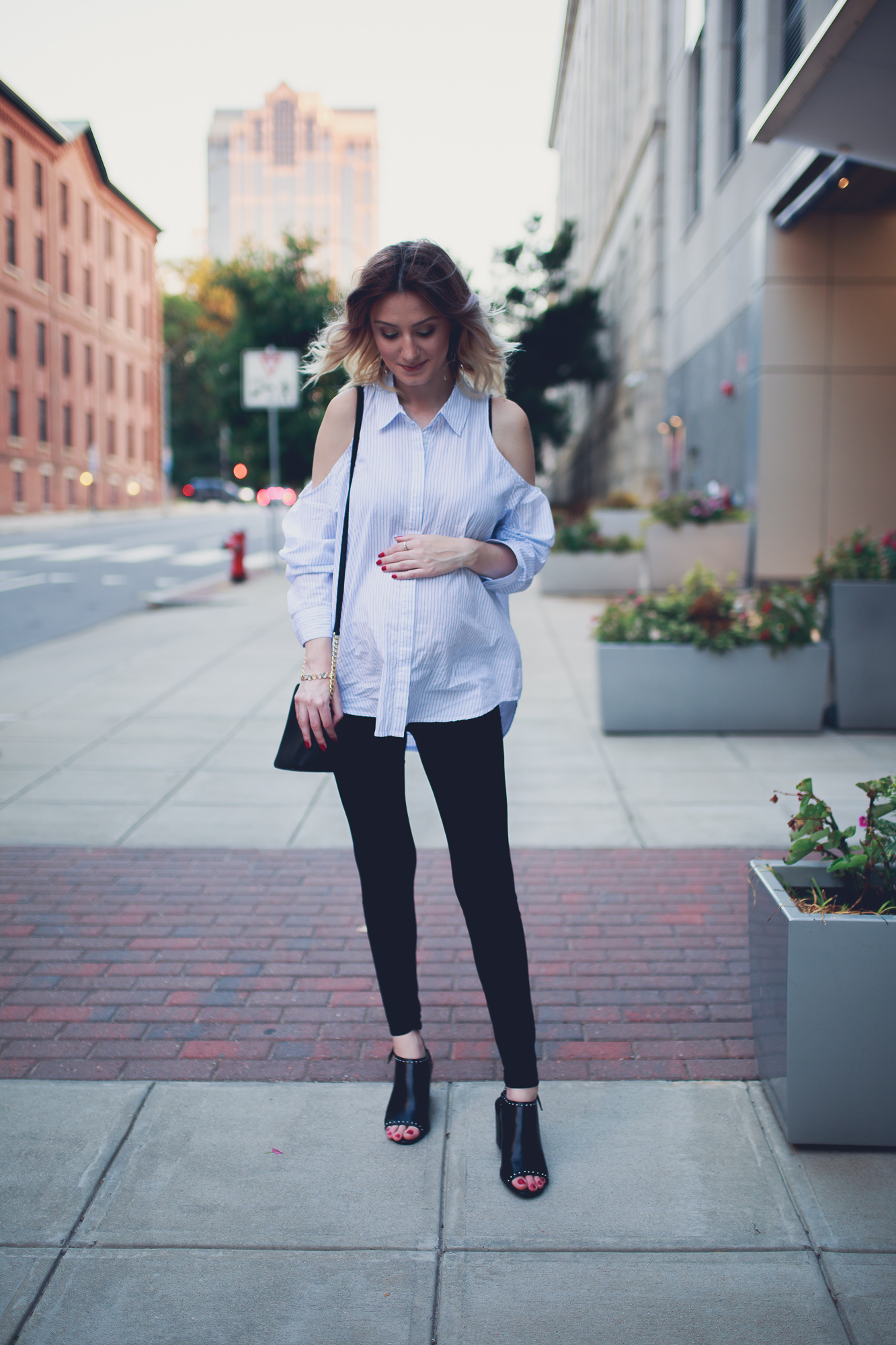 Fashion Blogger and lifestyle blogger Jessica Linn from Linn Style wearing a cold shoulder pinstripe button up blouse from Forever21, black leggings from Romwe, and black silver studded heels from Charming Charlie's also carrying a black and gold Michael Kors Purse. Photos taken in Downtown Raleigh North Carolina.