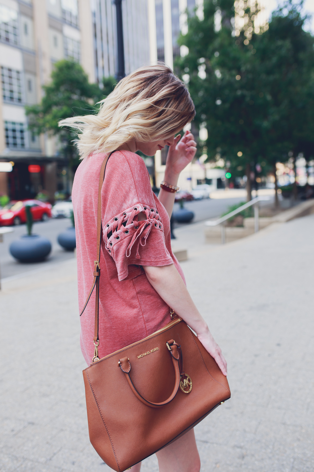 Lifestyle Fashion and beauty blogger Jessica Linn from Linn Style wearing a Forever21 sweater dress and Michael Kors purse in downtown Raleigh North Carolina. Non-maternity maternity outfits.