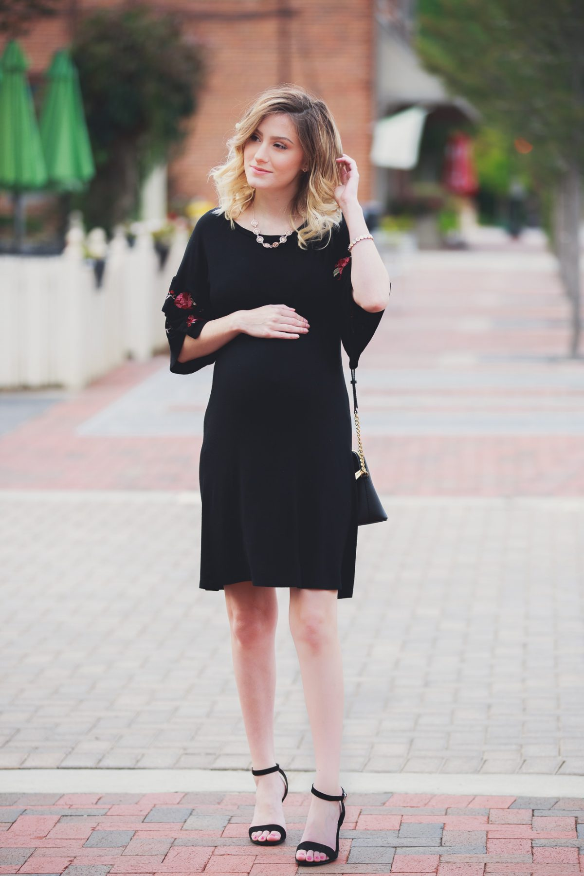 Fashion, lifestyle, and beauty blogger and vlogger Jessica Linn wearing a black ruffle sleeve dress with floral embroidery on the sleeves from Francesca's. Also carrying a Michael Kors purse and black heels from ASOS in Downtown Cary North Carolina.