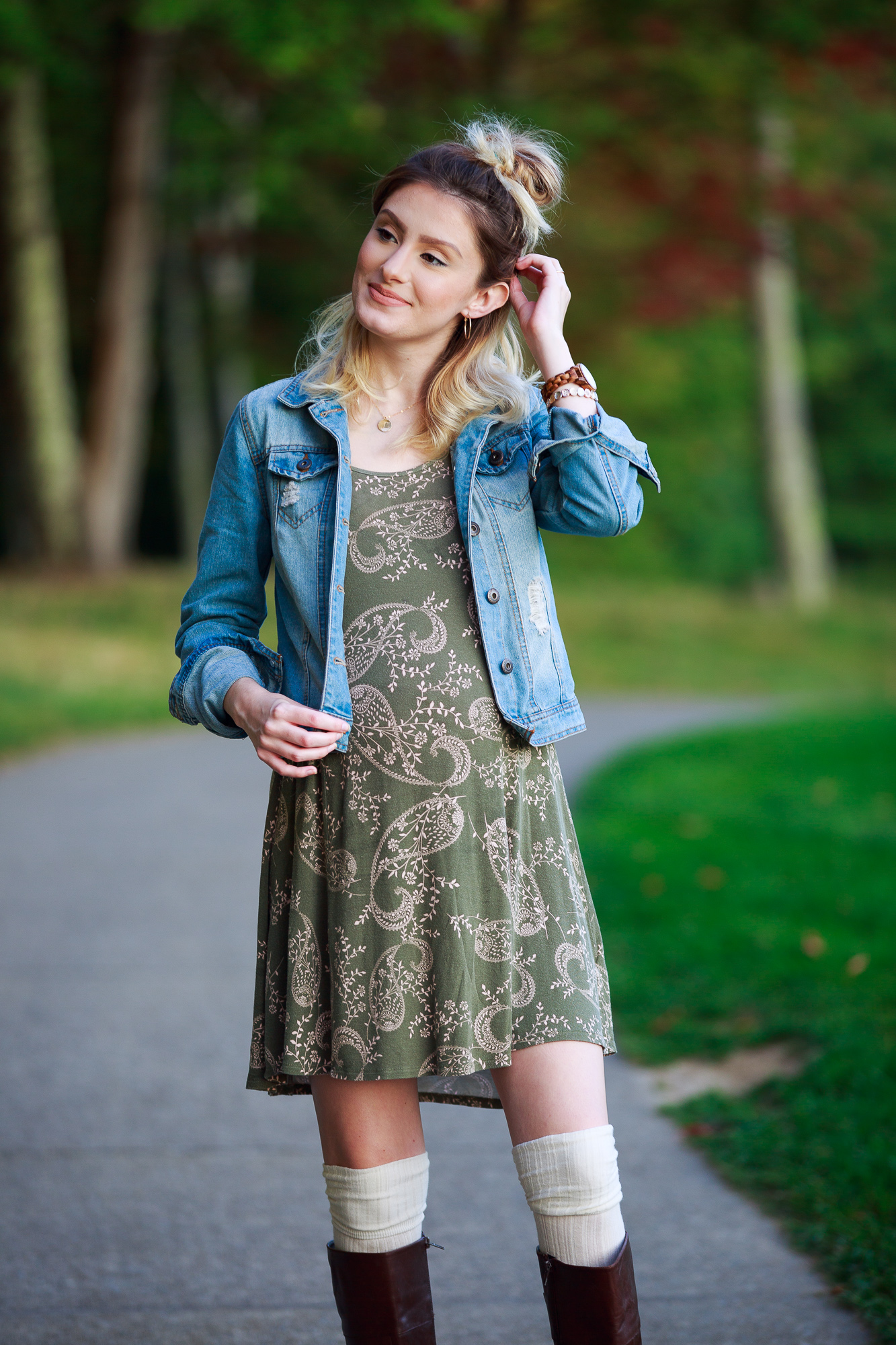 Lifestyle and fashion blogger Jessica Linn wearing a Charlotte Russe olive colored dress with a neutral paisley pattern, a denim jacket, thigh high socks, and Ralph Lauren boots. Perfect fall maternity outfit!