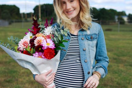 Lifestyle and fashion blogger Jessica Linn from Linn Style wearing a navy blue and white horizontal striped maternity dress from Target and a denim jacket. Shopping for pumpkins at the NC State Farmers Market for fall. October