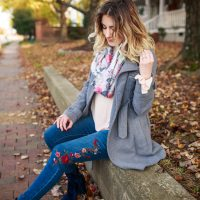 A New Day Clothing Brand From Target. Fashion and lifestyle blogger Jessica Linn from Linn Style wearing a pink ruffle bell sleeve sweater, floral embroidered skinny jeans, a gray peacoat, blue velvet booties, and a floral Scarf from World Market. Carrying a pearl gray Michael Kors purse