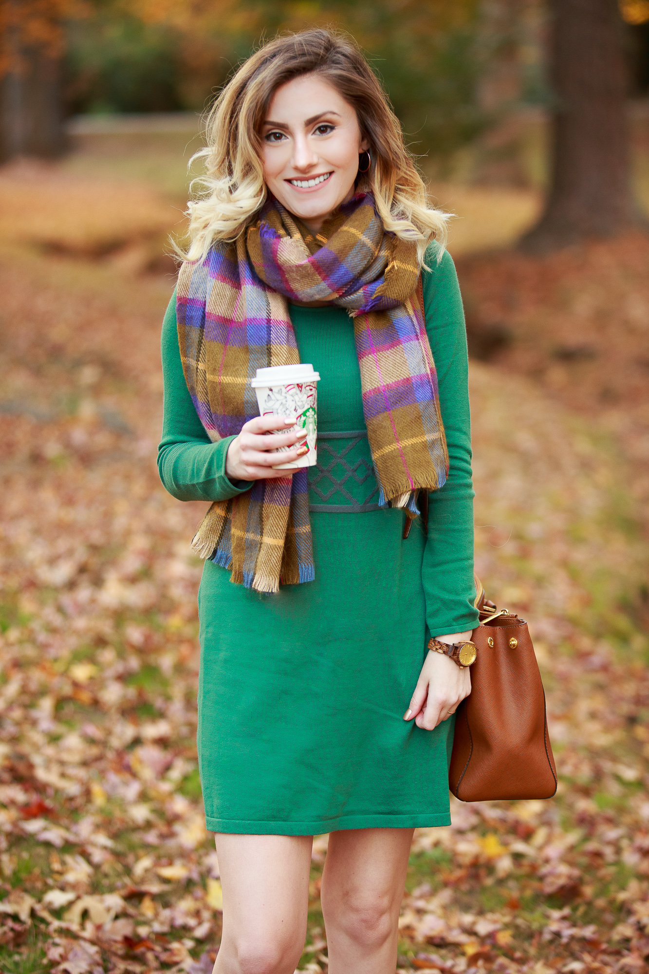 North Carolina fashion and lifestyle blogger Jessica Linn wearing a sweater dress from Aventura. Aventura clothes are made from organic sustainable materials promoting sustainable fashion. Also wearing fringe booties from Forever21, a green plaid scarf from Target, and a Michael Kors purse and a JORD wood watch.