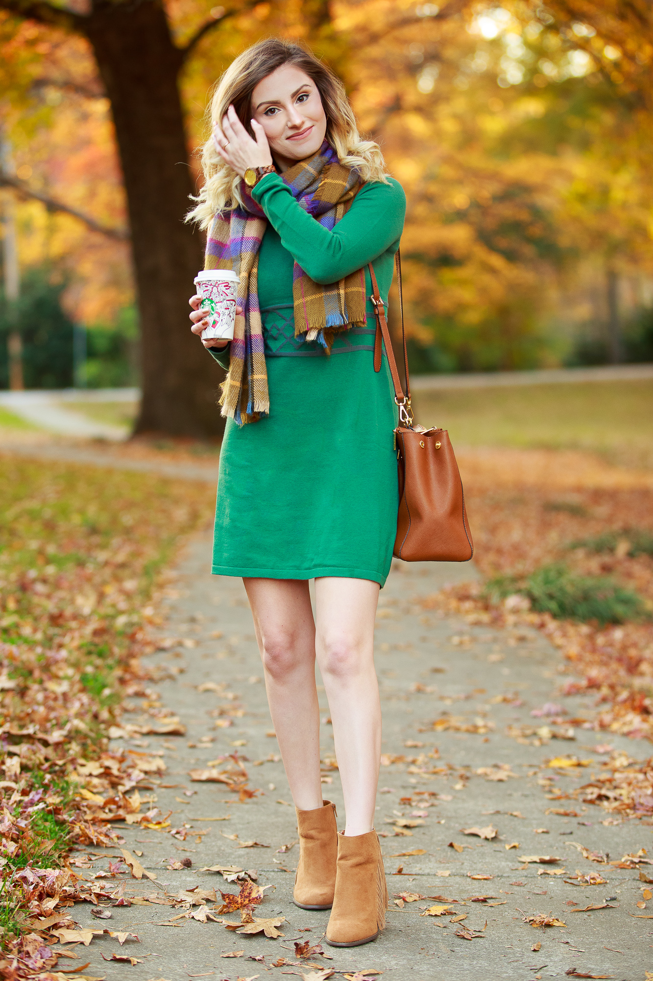 North Carolina fashion and lifestyle blogger Jessica Linn wearing a sweater dress from Aventura. Aventura clothes are made from organic sustainable materials promoting sustainable fashion. Also wearing fringe booties from Forever21, a green plaid scarf from Target, and a Michael Kors purse.