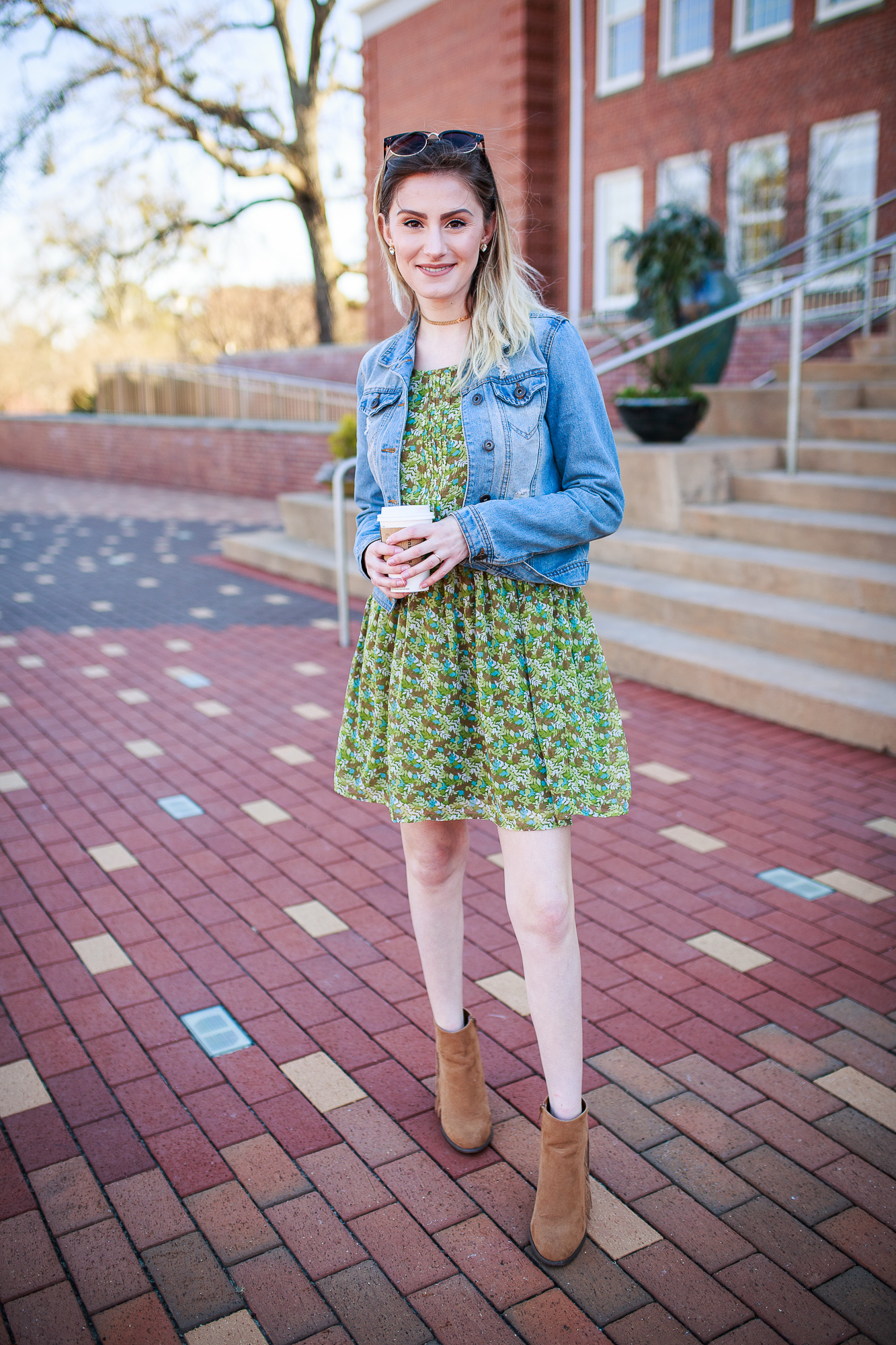North Carolina fashion and lifestyle blogger Jessica Linn wearing her version of spring trends. A floral print dress from Charming Charlie, fringe faux suede booties from Forever21, a denim jacket from Ross, and a gold choker from local Cary NC business CY Design Studio.