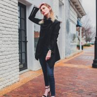 North Carolina fashion and lifestyle blogger Jessica Linn from Linn Style wearing a Welly Merck watch with a black draped coat, dark denim jeans from Target, and black faux suede strappy heels from ASOS. Photography by Joel Pagan taken in Downtown Cary NC