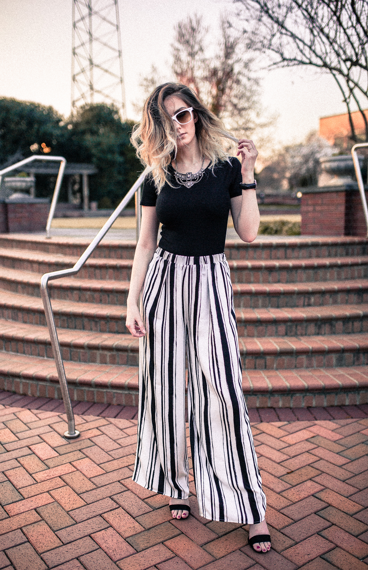 North Carolina fashion and lifestyle blogger Jessica Linn from Linn Style wearing a black Forever21 bodysuit and Forever21 black and white stripe palazzo pants. Paired with black faux suede strap sandal heels from ASOS, a Baublebar statement necklace from Target, a Welly Merck Roma watch, and Charming Charlie white sunglasses
