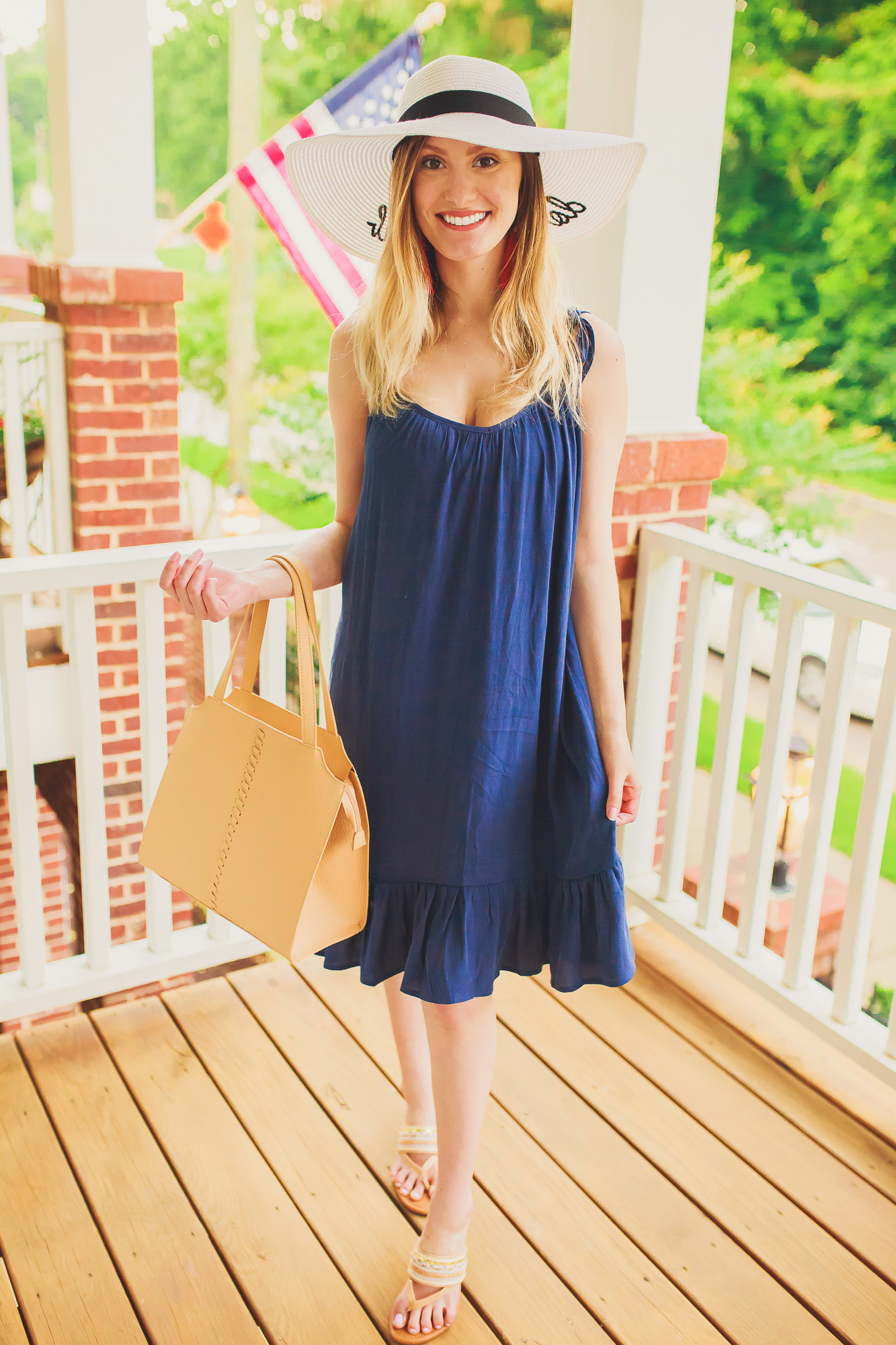 "What to Wear in The 4th of July | Fashion and lifestyle blogger Jessica Linn showing some Independence Day outfit inspiration and a cute red white and blue outfit in collaboration with local North Carolina business, Southern Chique Boutique. Navy blue spaghetti strap dress from Southern Chique Boutique, red tassel earrings and ""Do Not Disturb"" sun hat from Copper Bloom, purse by Universal Thread from Target, and sandals from Ross."