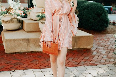 Pink bell sleeve romper with white stripes from Copper Bloom, layered tassel necklace from Baublebar, tassel earrings from Siam Hills Tribe, clutch from Anne Taylor. Summer outfit inspiration styles by North Carolina fashion and lifestyle blogger Jessica Linn.