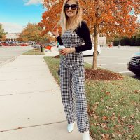 Fashion Inspiration by North Carolina fashion and lifestyle blogger Jessica Linn. Wearing a black and white checkered jumpsuit and white pointed toe boots.