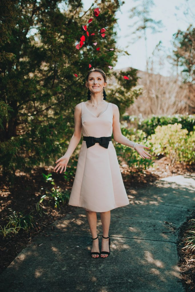 Valentines Day Outfit Inspiration | Kate Spade Fit & Flare Dress by popular North Carolina fashion and lifestyle blogger, Jessica Linn, owner and author or Linn Style and Babies, Love, & Lattes.  Jessica wearing a pale pink fit and flare dress with a black bow on the waist, black sandal heels, and throwing glitter heart confetti.