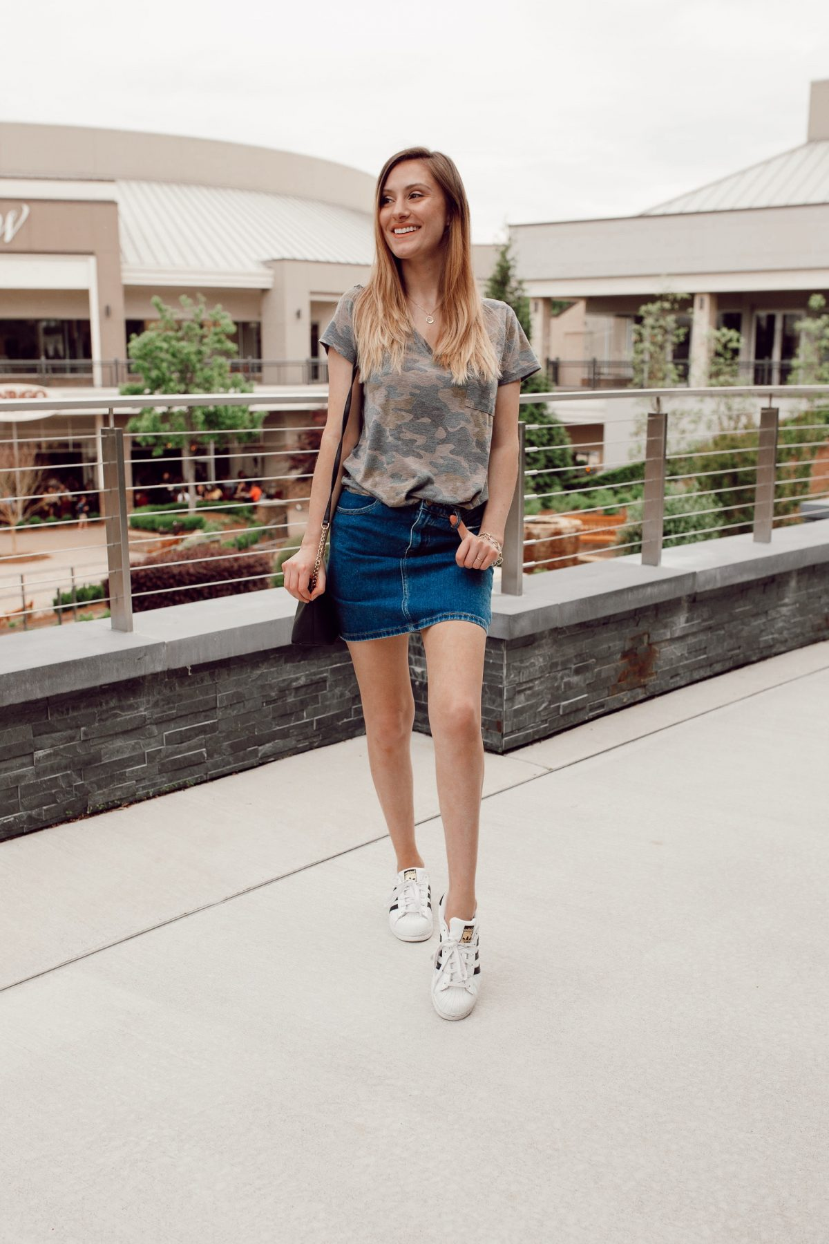 Sporty outfit inspiration with fashion blogger Jessica Linn wearing a Forever21 Denim skirt, Adidas shoes, and a camouflage t-shirt.