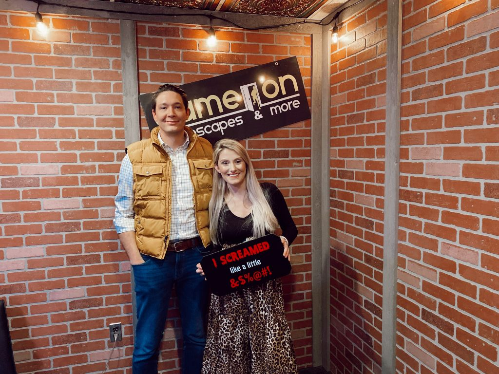 How To Wear A Non-Maternity Maxi Skirt While Pregnant by Jessica Linn.  Pregnant North Carolina fashion blogger Jessica Linn wearing a long leopard print skirt, black long sleeve shirt, and wenda cut-out booties at Game on Escape Rooms. With husband Joel Pagán.