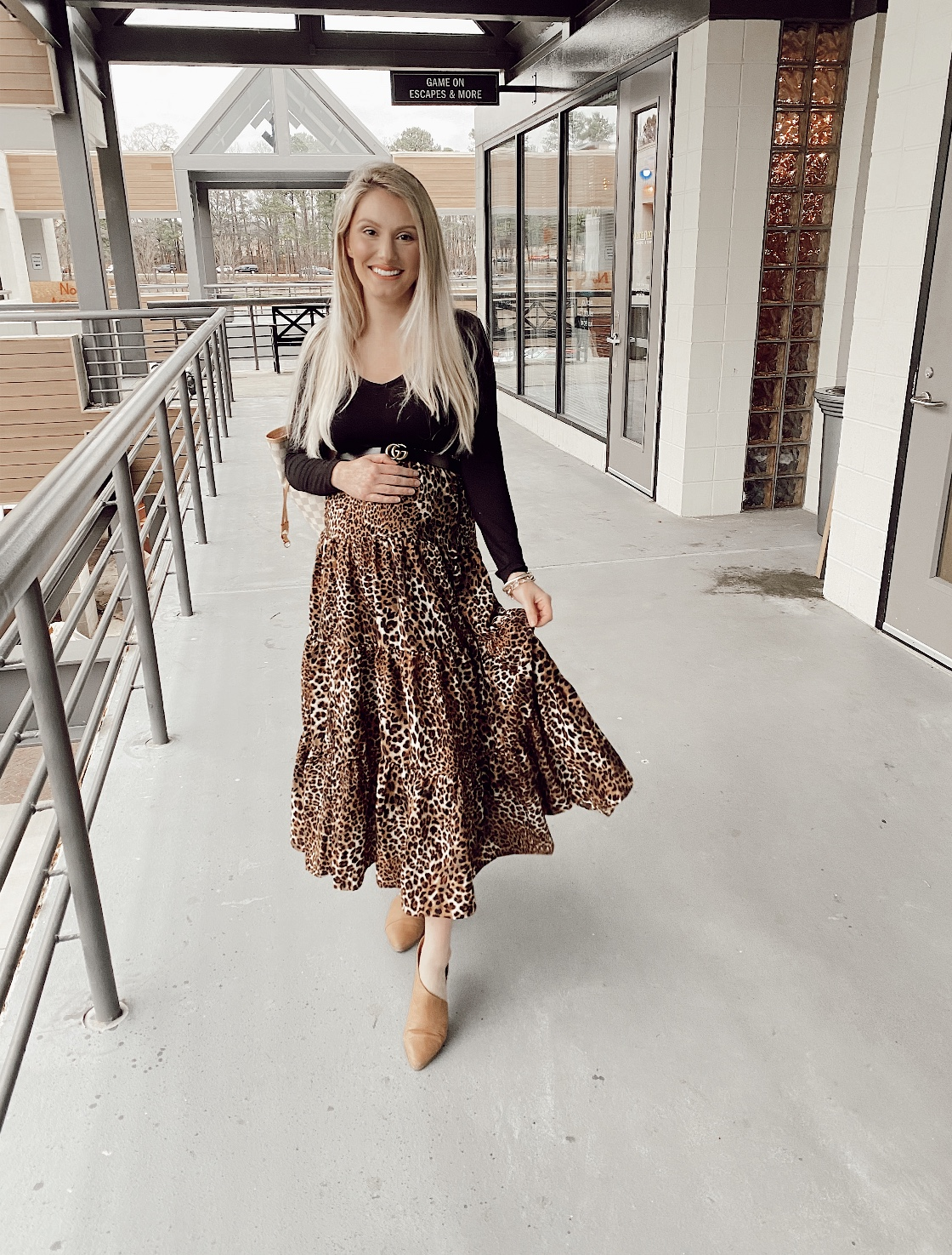How To Wear A Non-Maternity Maxi Skirt While Pregnant by Jessica Linn. Pregnant North Carolina fashion blogger Jessica Linn wearing a long leopard print skirt, black long sleeve shirt, and wenda cut-out booties at Game on Escape Rooms.